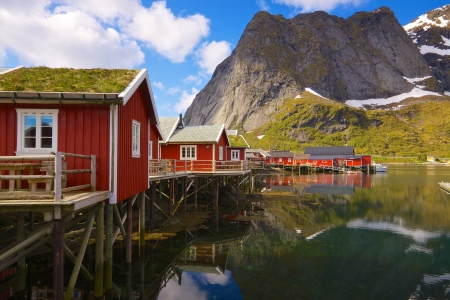 rorbu: Typical red rorbu fishing huts with sod roof on Lofoten islands in Norway reflecting on river