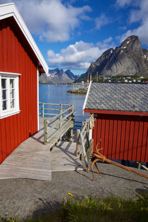rorbu: Red fishing rorbu huts by the fjord in town of Reine on Lofoten islands Stock Photo