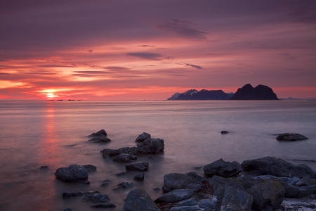 Midnight sun on Lofoten islands in Norway with island of Moskenesoya on the horizon