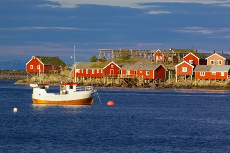 rorbu: Red fishing rorbu huts and fishing boat in town of Reine on Lofoten islands Stock Photo