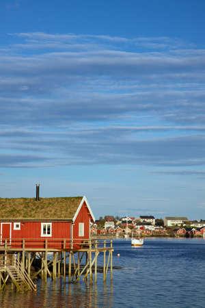 rorbu: Red fishing rorbu hut by the fjord in town of Reine on Lofoten islands