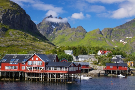 Picturesque village on Lofoten islands in Norway surrounded by high peaks of mountains