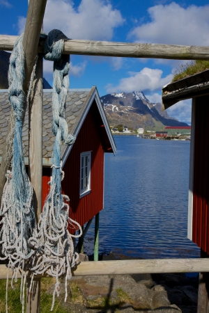 rorbu: Traditional red fishing rorbu huts by the fjord in town of Reine on Lofoten islands