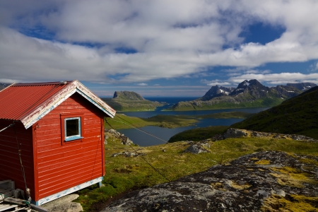 Picturesque panorama on Lofoten islands with red mountain cabin, fjords and high mountain peaks surrounding them Stock Photo