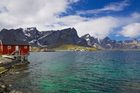 fishing hut: Typical norwegian fjord with fishing hut and high mountains peaks towering above the sea