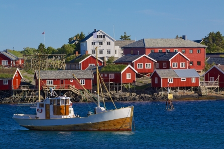 Red fishing rorbu huts and fishing boat in town of Reine on Lofoten islands Stockfoto