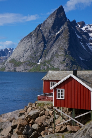 rorbu: Traditional red fishing rorbu hut on the coast of fjord on lofoten islands in Norway Stock Photo