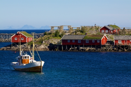 rorbu: Traditional fishing boat with red rorbu fishing houses on Lofoten islands in Norway