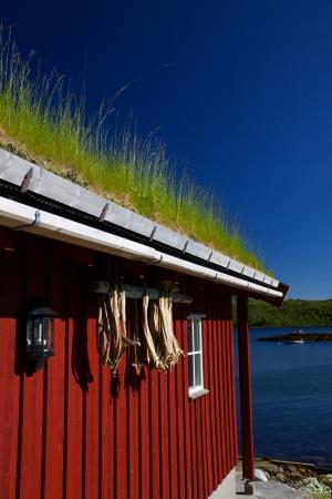 Detail der traditionellen norwegischen Fischerhütte mit getrockneten Stockfisch Stücke hängen an der roten Wand Standard-Bild