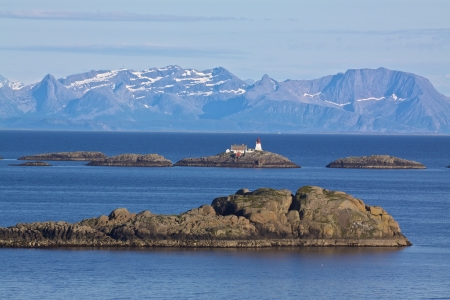 Norwegian coast with tiny rocky islets, picturesque lighthouse and high mountains in the background photo