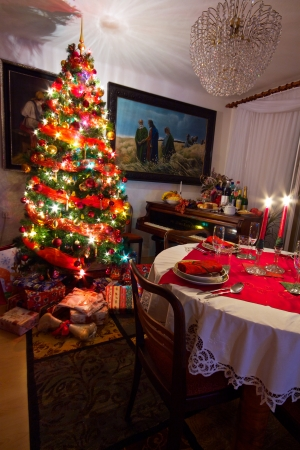 Cozy room with presents under decorated Christmas tree, old piano and table ready for Christmas dinner Stock Photo - 15129753