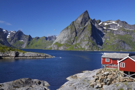 fishing hut: Scenic fjord on Lofoten islands with typical red fishing hut and towering mountain peaks Stock Photo