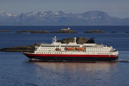 islets: Large passenger ship cruising along norwegian coast with tiny rocky islets near Lofoten islands