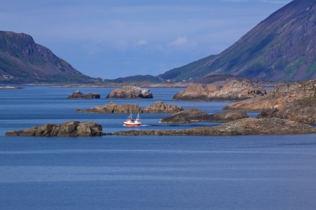 Small fishing boat passing between rocky islets in fjord on Lofoten islands, Norway photo