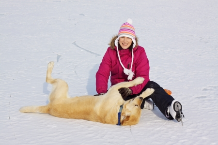 Joyful attractive girl with ice skates playing with her dog on frozen lake photo