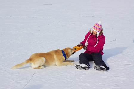 Happy attractive girl with ice skates playing with her dog on frozen lake photo