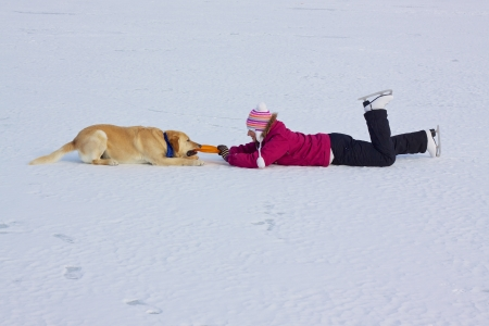 Girl with ice skates playing with her dog on frozen lake photo