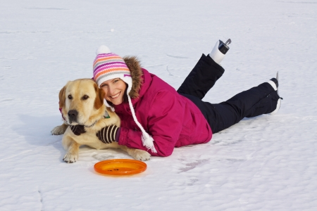 Beautiful joyful young girl with ice skates laying with her dog in snow on frozen lake photo