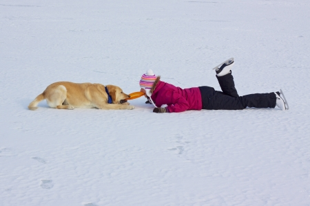 Girl with ice skates playing with her dog on frozen lake pulling the dog toy with her teeth photo