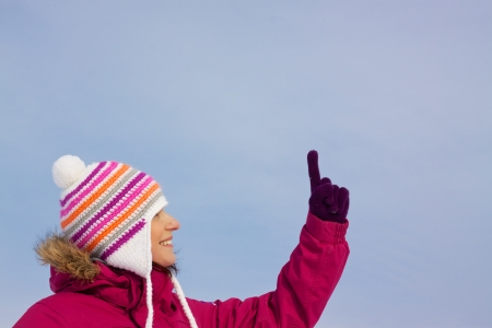 Smiling attractive girl wearing knitted winter cap and gloves pointing upwards with her finger, place for your copy photo
