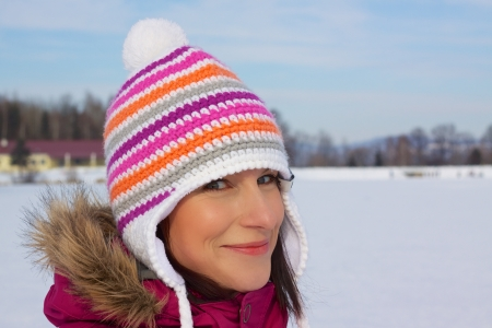 Smiling young woman wearing knitted winter cap with natural winter background photo
