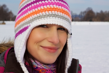 Closeup of smiling young woman wearing knitted winter cap with natural winter background photo