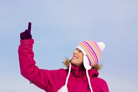 Smiling attractive girl wearing knitted winter cap and gloves pointing upwards with her finger