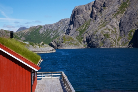 rorbu: Traditional red fishing rorbu hut with sod roof on Lofoten islands in Norway Stock Photo