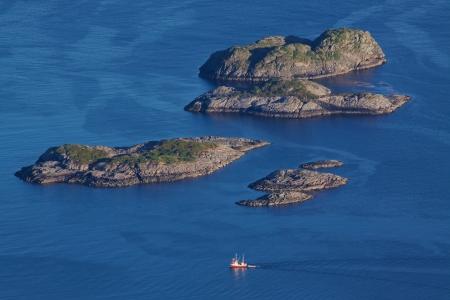 islets: Bird eye view of fishing boat sailing between by rocky islets near Henningsvaer on Lofoten islands in Norway Stock Photo