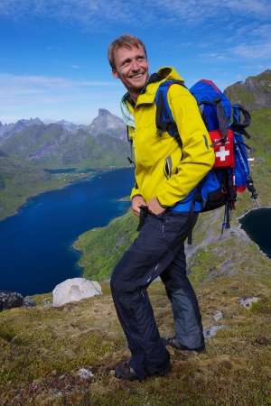Young smiling active man with backpack hiking on picturesque Lofoten islands in Norway on sunny day photo