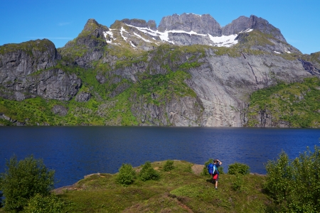 Young hiker with backpack standing by fjord on Lofoten islands in Norway on sunny day photo