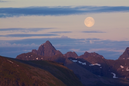 Full moon rising above scenic mountain peaks lit by midnight sun in arctic Europe photo
