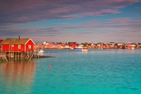 rorbu: Typical red rorbu hut with sod roof in town of Reine on Lofoten islands in Norway lit by midnight sun Editorial