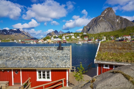 rorbu: Red fishing rorbu huts by the fjord in town of Reine on Lofoten islands in Norway during summer