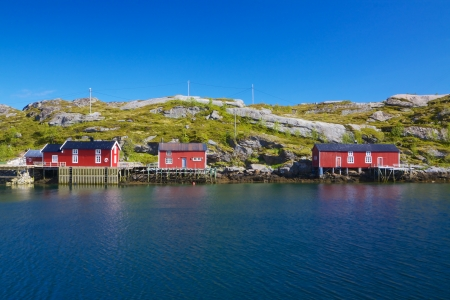rorbu: Red fishing rorbu huts by the fjord on Lofoten islands in Norway during summer Editorial