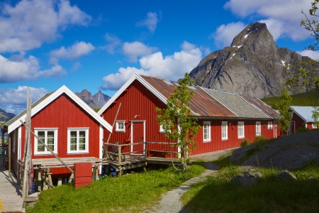 Red fishing rorbu huts by the fjord in town of Reine on Lofoten islands in Norway