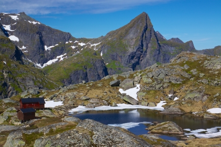 Scenic norwegian panorama with mountain cabin by lake on Lofoten islands photo