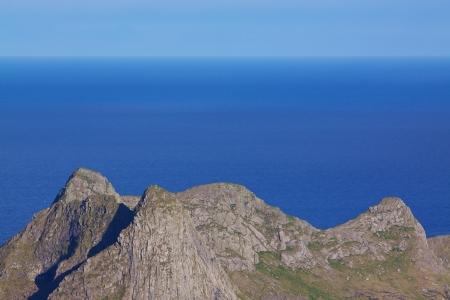 Rocky peaks on the coast of norwegian sea on sunny summer day photo
