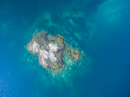 islet: Scenic aerial view of tiny rocky islet in turquoise sea
