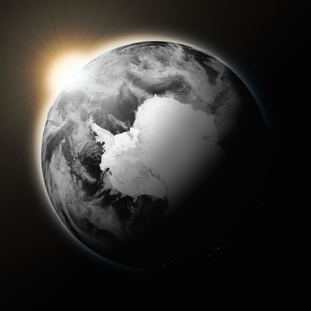 background antarctica: Sun over Antarctica on dark planet Earth isolated on black background.