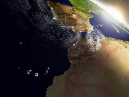 city lights: Morocco with surrounding region during sunrise as seen from Earths orbit in space. 3D illustration with highly detailed realistic planet surface, clouds and city lights. Stock Photo