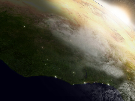 city lights: Ivory Coast, Ghana and Burkina Faso with surrounding region during sunrise as seen from Earths orbit. 3D illustration with highly detailed realistic planet surface, clouds and city lights.