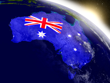 Australia with embedded flag on planet surface during sunrise. 3D illustration with highly detailed realistic planet surface and visible city lights. Stock Photo