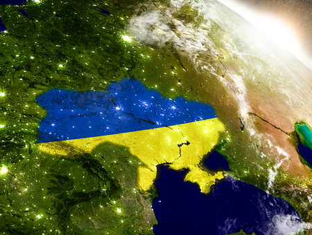 Ukraine with embedded flag on planet surface during sunrise. 3D illustration with highly detailed realistic planet surface and visible city lights. Stock Photo