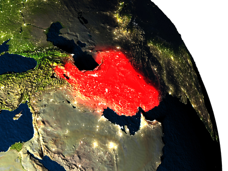 Iran highlighted in red on model of planet Earth with very detailed land surface and visible city lights. 3D illustration. Stock Photo