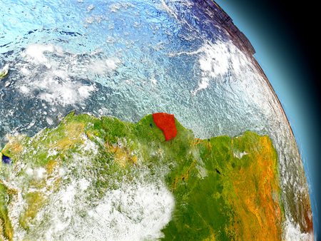 French Guiana in red on model of planet Earth with embossed countries and visible country borders. 3D illustration with clouds and reflective ocean waters.
