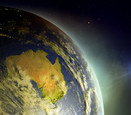 Australia as seen from Earths orbit during sunrise with brightly glowing atmosphere from the sunlight. 3D illustration with detailed planet surface.