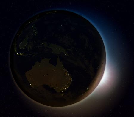 Soleil se levant au-dessus de l'Australie sur la planète Terre vue de l'espace. Illustration 3D avec des lumières de la ville réelle éclairant la surface. Banque d'images - 80620868