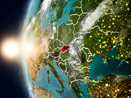 Satellite view of Slovakia highlighted in red on planet Earth with clouds and visible country borders during sunset. 3D illustration.