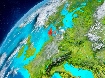 Country of Denmark in red on planet Earth with atmosphere. 3D illustration. Stock Photo